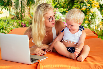 fair-haired one year old female kid looking at a laptop cartoon with mother blonde freelancer surfer on sunbeds resort summer beach.business woman freelancing and daughter relaxing by the sea