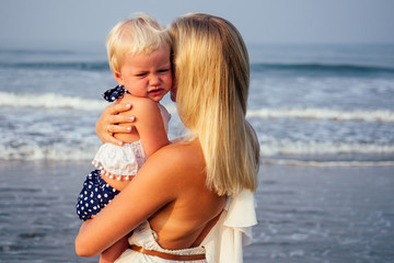 mother daughter having fun resting on the beach. Family vacation travel . Caucasian female with toddler baby at ocean .