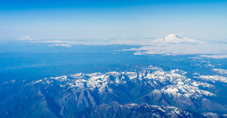 Washington state volcanoes are showing up over the clouds.