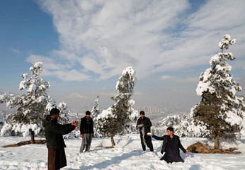 Afghan youth take pictures of each other after the first snow in winter on the snow-covered ground in Kabul