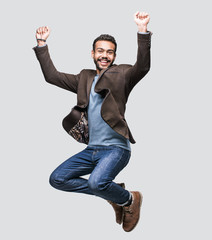 Portrait of handsome smiling young man celebrating. Jumping laughing joyful cheerful men studio shot. Isolated on gray background