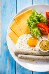 English breakfast - fried egg,sausages,bun and vegetables