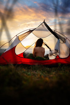 Naked woman sitting in tent in sleeping bag and enjoy the scenery in the mountains. Incredible cloudy sky at sunrise or sunset. Trekking concept. Relaxing, feeling alive, got freedom from work