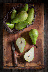Green Pears in an old wire basket on wooden box