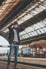 stylish bearded hipster tourist with backpack behind his shoulder on the platform of the railway station with a metal vault