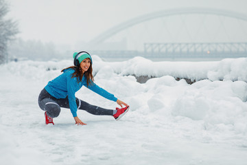 Young woman stretching legs on snowy day in the city