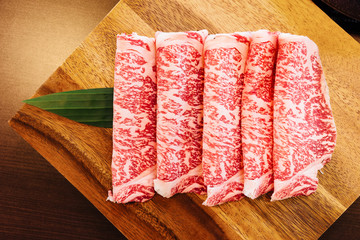 Premium Rare Slices Wagyu A5 beef with high-marbled texture on square wooden plate served for Sukiyaki and Shabu. Wall mural