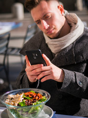 Side view of a handsome young man taking a photo of his food in the restaurant outside