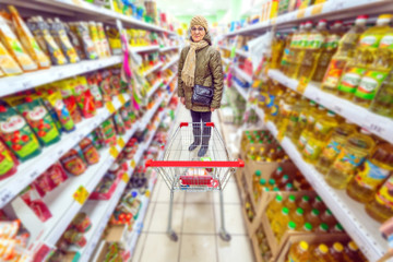 Beautiful mature woman chooses products in a large supermarket.