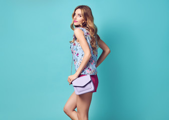 Fashion beautiful young blonde woman smiling in floral blouse, shorts with handbag posing over blue background. Sexy adorable girl with Stylish wavy Hairstyle, makeup.