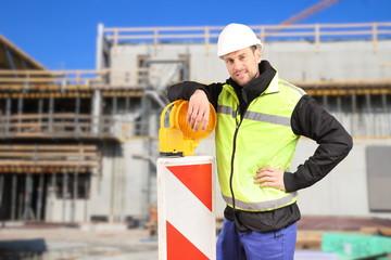 Bauarbeiter lehnt auf Barke vor Baustelle