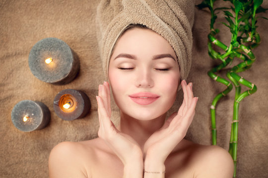 Beautiful spa woman with a towel on her head lying and touching face skin. Skincare. Beauty smiling model girl in spa salon