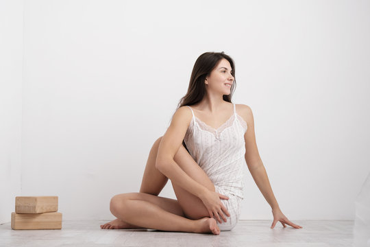 Woman in home clothes doing exercises on the floor. Balances on the blocks.