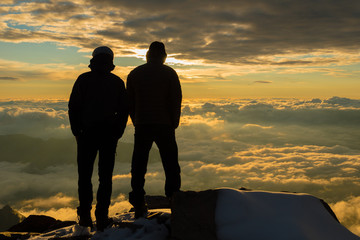 Friends above clouds in alps watching sunset from the summit