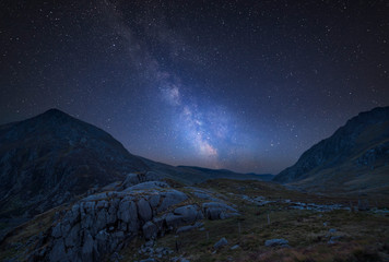 Digital composite Milky Way image of Beautiful dramatic landscape image of Nant Francon valley in Snowdonia