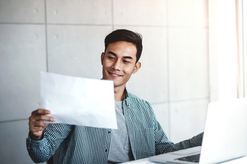 Happy Young Asian Businessman Working on Computer Laptop in his Workplace. Smiling and looking at Paper Worksheet