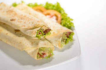 Fresh tortilla wraps with vegetable filling and chicken - close up