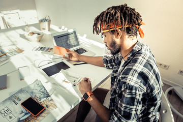Interior designer with dreadlocks wearing red headband drawing sketches