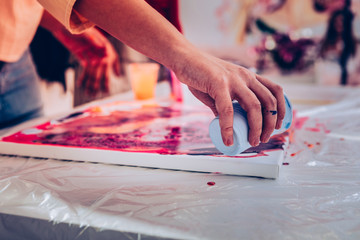Young artist holding glass with paint while working on picture