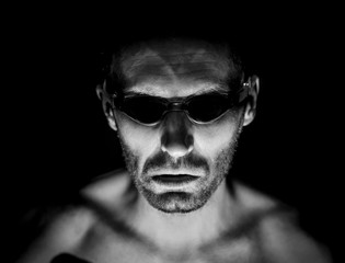 Portrait of unshaven adult caucasian man in swimming glasses. He smiles like maniac and seems like madness. Black and white shot, low-key lighting. Isolated on black.