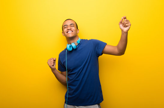 African american man with blue t-shirt on yellow background enjoy dancing while listening to music at a party