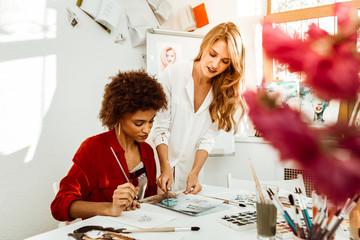 Beautiful stylish blonde-haired art teacher helping her student