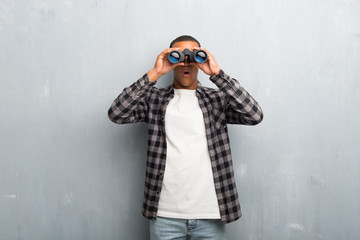Young african american man with checkered shirt and looking for something in the distance with binoculars