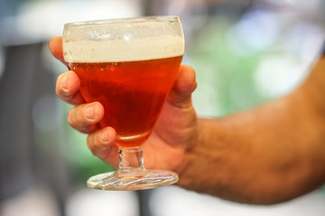 Human hand holding a glass full of red beer
