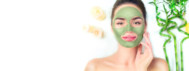 Spa. Young woman applying facial green clay mask in spa salon. Beauty treatments. Skincare. Top view