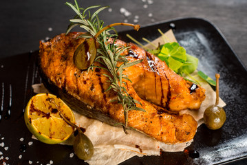 Grilled big fish steak on the black wooden background