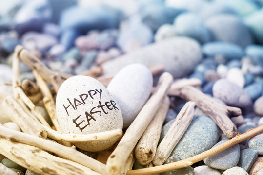 Easter egg from a stone with the inscription Happy Easter in a decorative nest from brushwood on the sea pebble beach.