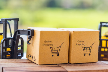 Cardboard boxes with shopping cart symbol on wooden block and mini crane truck nearby with natural background. Logistics and transportation management ideas and Industry business commercial concept.