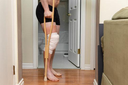 bottom half torso of man with bandaged knee on crutches