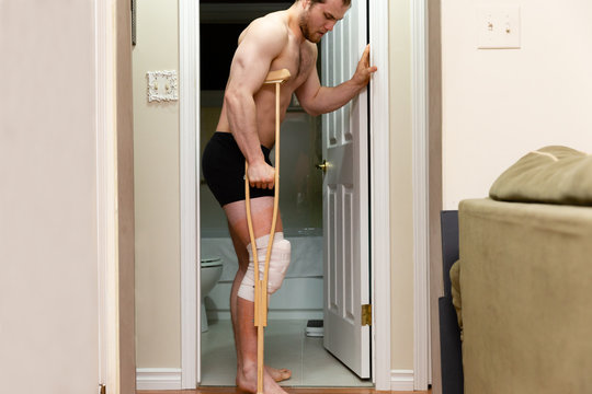 caucasian man standing with crutches after knee surgery.