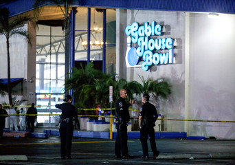 Police officers investigate a shooting at a bowling alley in the Los Angeles suburb of Torrance