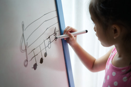 Young Asian girl kid winging music key on standing whiteboard. She practicing write down the key note. Music learning concept.