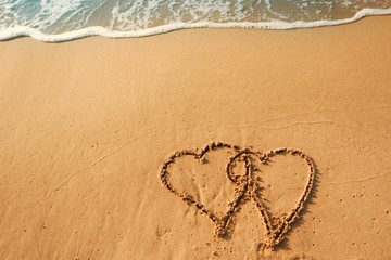 Valentine's day concept, two heart shape writing on sand beach with blue waves ocean.