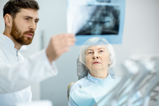 Worried elder woman during the consultation with handsome dentist showing panoramic x-ray in the dental office