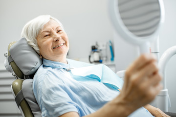 Happy elderly woman enjoying her beautiful toothy smile looking to the mirror in the dental office