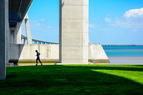 Man Running under Beautiful Vasco da Gama Bridge over Tejo River in Lisbon, Portugal