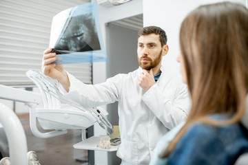 Handsome dentist checking panoramic x-ray of a jaw during the medical consultation with woman patient in the dental office