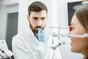 Portrait of a thoughtful dentist during the work with young woman patient in the dental office