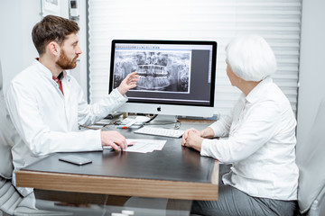 Senior woman patient during the medical consultation with dentist showing dental x-ray on the monitor
