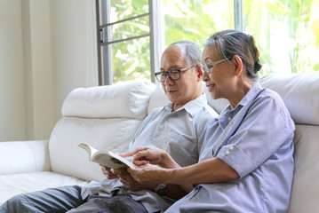 Asian senior couple sitting on sofa and reading a book in living room. They read the book with smile while wife pointing at the book and have some conversation . Happy retirement life concept.