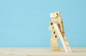 wooden dummy climbs a dangerously unstable structure and risks falling.