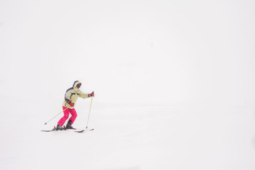Woman is skiing down the slope in a snowy day.Winter sport with a copy space