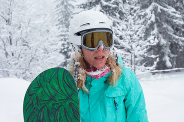Portrait of a girl with a snowboard and winter sport equipment