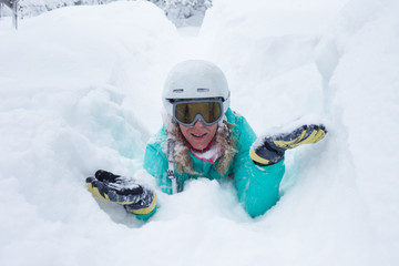 Girl with winter sport equipment laying in deep snow in a mountain