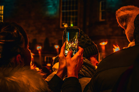 Woman taking pictures with her phone at the torchlight procession preceding new years eve or Hogmanay  in Edinburgh Scotland