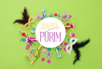 Purim celebration concept (jewish carnival holiday) over green wooden background. Top view.
